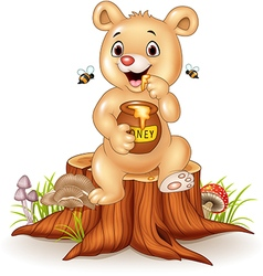 Cute baby bear holding honey pot on tree stump vector