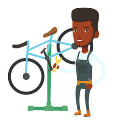 African bicycle mechanic working in repair shop vector
