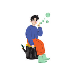 Boy sitting on stump and blowing soap bubbles vector