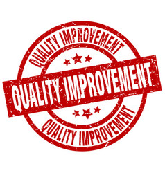 Quality improvement round red grunge stamp vector