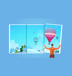 man looking in window at colorful air balloons vector image