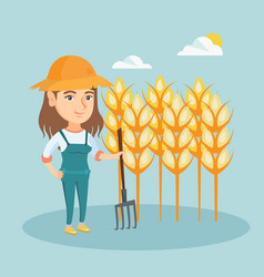 Young farmer standing in a field with pitchfork vector
