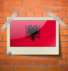 Flags Albania scotch taped to a red brick wall vector