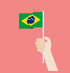 hand holding up brazil flag vector image