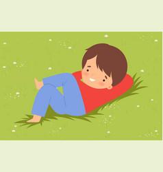Cute boy lying down on green lawn kid lying on vector