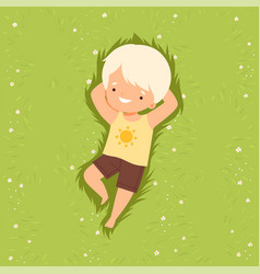 Adorable smiling boy lying down on green lawn vector