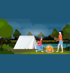 couple hikers making fire girls holding firewood vector image