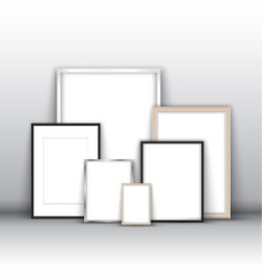 Blank picture frames against a wall vector