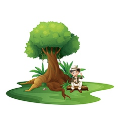 A boy sitting under the big tree vector image vector image