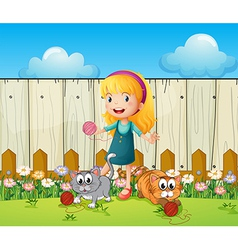 A girl playing with her cats inside the fence vector
