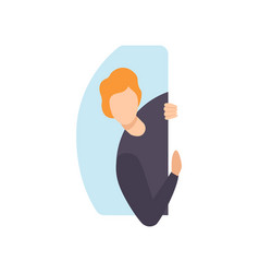 Young man peeping from behind a wall vector