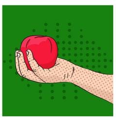Hand holding red apple on green background vector