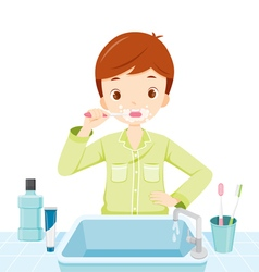 Boy In Pyjamas Brushing His Teeth In Bathroom vector