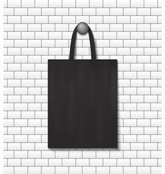 Fashion eco tote bag mockup hanging on wall vector