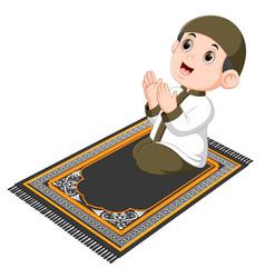 Boy is praying on brown prayer rug vector