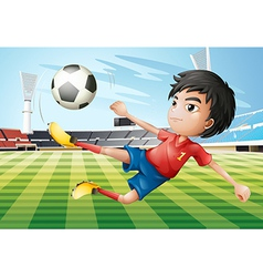 A boy playing soccer at the soccer field vector