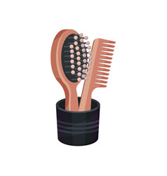 wooden hairbrush and comb in black cup vector image