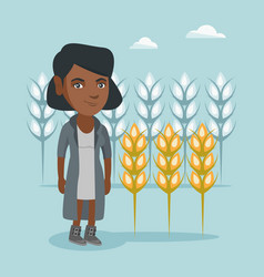 Young african farmer standing in a wheat field vector