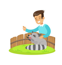 smiling little boy petting and feeding a raccoon vector image