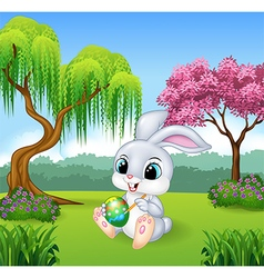 Cartoon little bunny painting an egg vector image