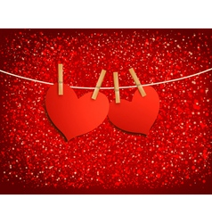 Two red loving hearts hanging on a rope vector image