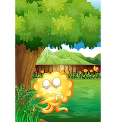 A yellow monster under the tree in the gated yard vector image vector image