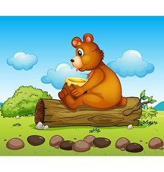 A bear sitting down on the trunk of a tree vector
