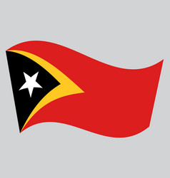 flag of east timor waving on gray background vector image vector image