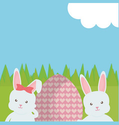 cute rabbits with easter egg painted in the field vector image