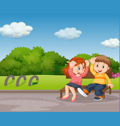 Boy and girl sitting in park vector