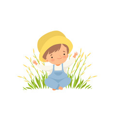 Cute happy boy sitting on green meadow adorable vector