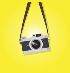 Hanging vintage camera over yellow background vector