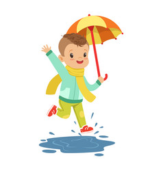Cute little boy holding colorful umbrella playing vector
