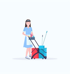 Woman housemaid holding trolley cart with supplies vector