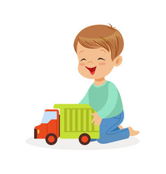 Cute happy little boy sitting on the floor playing vector