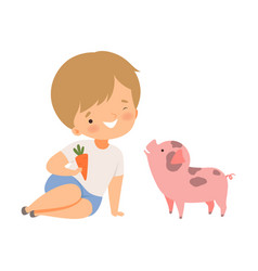 Little boy holding carrot to feed his pig pet vector
