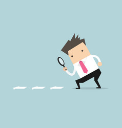 businessman searching through a magnifying glass vector image