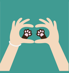 two womans hands holding cute cat dog paw print vector image