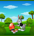 easter bunny painting easter eggs in the park vector image vector image