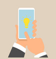 hand holding smartphone with light bulb on display vector image vector image