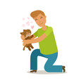 care for pet young man holds a cute stray kitten vector image