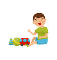 cute boy sitting on the floor playing with toys vector image vector image