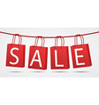 Realistic red shopping bags hanging on rope with vector image