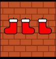 three christmas socks for gifts hanged on a brick vector image