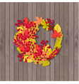 wreath of autumn leaves on a wooden background vector image