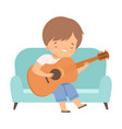 cute boy sitting on sofa and playing guitar kids vector image vector image