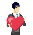 young asian groom holding a big red heart vector image vector image
