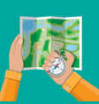 folded paper city map and compass in hands vector image