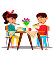 two hungry little asian kids at the table eating vector image vector image