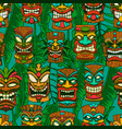 seamless pattern with tiki idols and palm leaves vector image